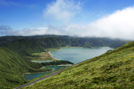 crater lake: amazing beautiful landscape view of crater volcano lake in Sao Miguel island of Azores in Portugal with green mountains and turquoise water reflecting sky in holiday destinations and travel concept Stock Photo