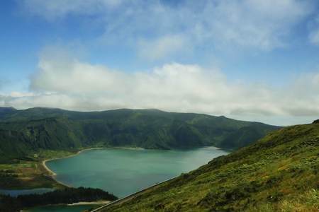 holiday destinations: amazing beautiful landscape view of crater volcano lake in Sao Miguel island of Azores in Portugal with green mountains and turquoise water reflecting sky in holiday destinations and travel concept Stock Photo