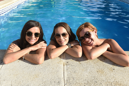 group of three happy beautiful young girl friends having bath in swimming pool together having fun enjoying summer at vacation resort smiling in women holiday concept Stock Photo