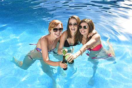 group of three young attractive happy girl friends having bath in swimming pool together having fun enjoying drinking beer cheering toast at summer vacation resort smiling in women holiday concept