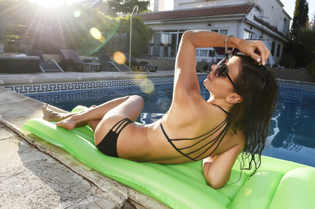 young sexy woman in bikini and sunglasses with fit beautiful body having suntan relaxing on airbed at swimming pool of vacation hotel resort in summer enjoying holidays with sun lens flare on sunset Stock Photo