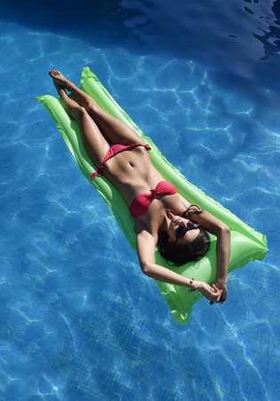 sunbath: young happy beautiful woman in bikini and sunglasses lying relax on float airbed at vacaction hotel resort swimming pool in Summer enjoying holidays having sunbath with tan body