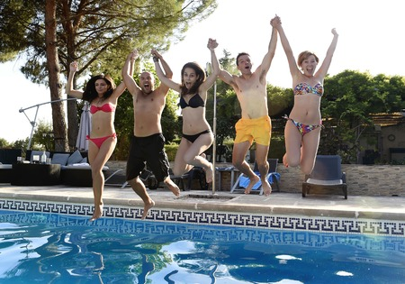 group of friends young happy attractive men and women in bikini jumping in the air to the water holding hands at hotel resort swimming pool having fun excited in boys and girls summer holidays Stock Photo