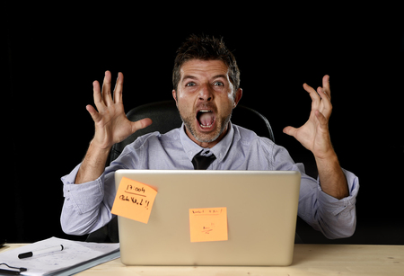 work load: young crazy stressed businessman screaming desperate working in stress with laptop computer heavy work load isolated on office desk black background in overwork overtime concept