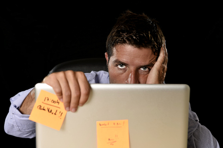 work load: young attractive tired businessman in shirt and tie tired and overwhelmed by heavy work load exhausted at office desk with laptop computer in business stress overwork and overtime concept Stock Photo