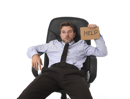young attractive tired and wasted businessman sitting on office chair asking for help in stress and frustrated face expression isolated on white background in work and business problem concept