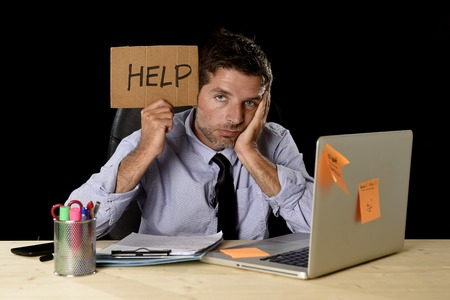 work load: young desperate businessman suffering stress working at office computer desk holding sign asking for help looking tired exhausted and overwhelmed by heavy work load isolated on black background