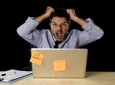 work load: young crazy stressed businessman screaming desperate pulling hair in stress with laptop computer heavy work load isolated on office desk black background in overwork overtime concept Stock Photo