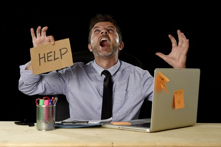 work load: young overworked businessman suffering stress working at office computer desk holding sign asking for help screaming crazy desperate by heavy work load isolated on black background Stock Photo