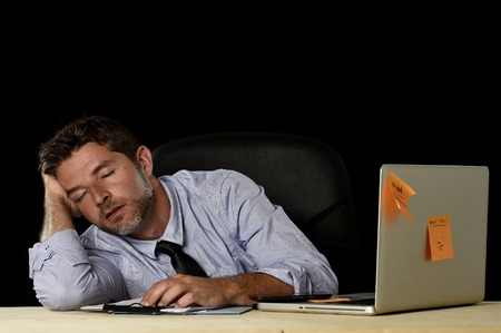 long hours: young attractive businessman sleeping wasted and tired at office computer desk in long hours of work late at night and business stress concept isolated in black background Stock Photo