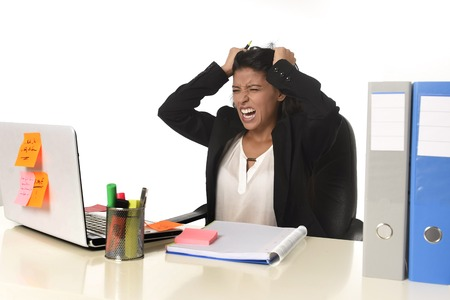 pulling beautiful: young beautiful latin businesswoman suffering stress working at office computer desk looking worried and desperate having problem pulling her hair  at work in overwork concept Stock Photo