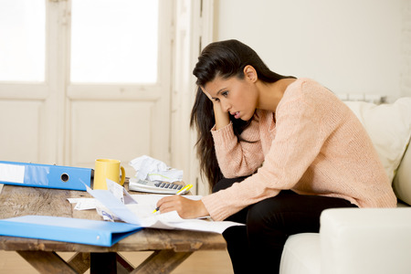 Amazing Young Sad Attractive Latin Woman At Home Living Room Couch Calculating  Monthly Expenses Worried In Stress