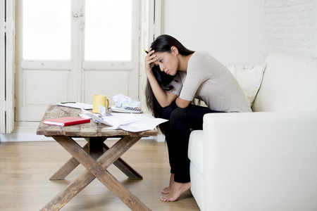 sad latin woman at home living room couch calculating monthly expenses worried in stress with bank papers and documents in paying taxes , mortage debt and cost of living concept