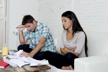 mortage: young sad couple at home living room couch calculating monthly expenses worried in stress with bank papers and documents in paying taxes , mortage debt and cost of living concept