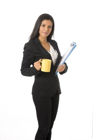 businesswoman suit: corporate portrait young attractive latin businesswoman in formal office suit smiling happy holding folder and coffee mug standing isolated on white background in business project presentation
