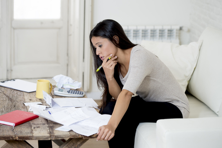 beautiful sad woman at home living room couch calculating monthly expenses worried in stress with bank papers and documents in paying taxes , mortage debt and cost of living concept Stock Photo