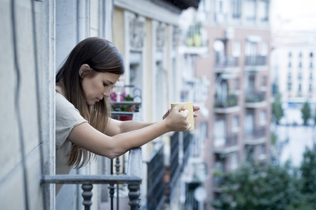 young sad beautiful woman suffering depression looking worried and wasted on home balcony with an urban view drinking tea cup in lonely depressed and desperate female concept