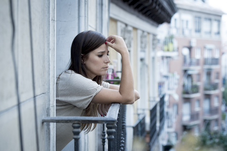 wasted: young sad beautiful woman suffering depression looking worried and wasted on home balcony with an urban view in lonely depressed and desperate female concept