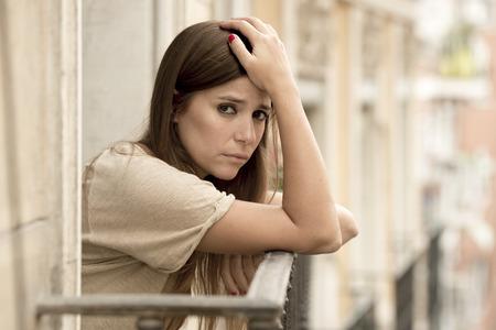 joven triste que la depresión que sufren hermosa mujer con cara de preocupación y no perdió en el balcón casa con una vista urbano en concepto de mujer deprimida y desesperada solitario