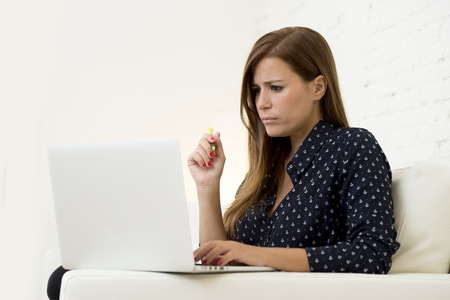 30s: young beautiful 30s woman using laptop computer networking or online internet shopping at home couch modern living room relaxed and thoughtful in technology and female domestic lifestyle