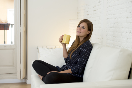 calm woman: young attractive woman sitting comfortably at modern apartment  living room home couch enjoying a cup of hot tea or coffee smiling happy and relaxed in female domestic lifestyle concept Stock Photo