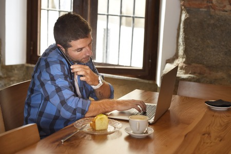 businessman working at his computer: young attractive businessman or student on his 30s wearing casual clothes working or studying with laptop computer at coffee shop busy talking on mobile phone in modern business concept
