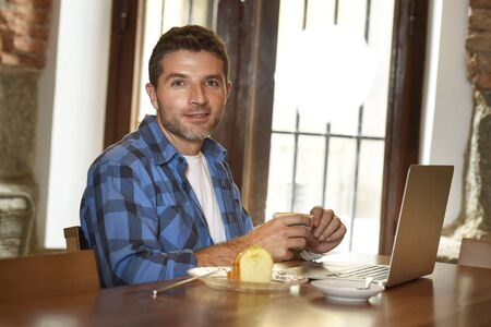 businessman working at his computer: young attractive businessman or student on his 30s wearing casual clothes working or studying with laptop computer at coffee shop drinking tea cup and cake in modern business self employed concept