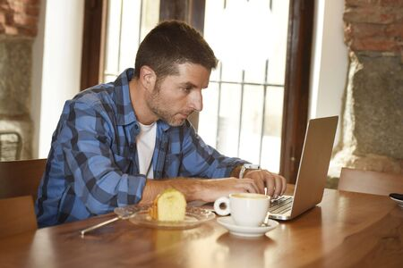 self employed: young attractive businessman or student on his 30s wearing casual clothes working or studying with laptop computer at coffee shop having tea cup and cake in modern business self employed concept Stock Photo