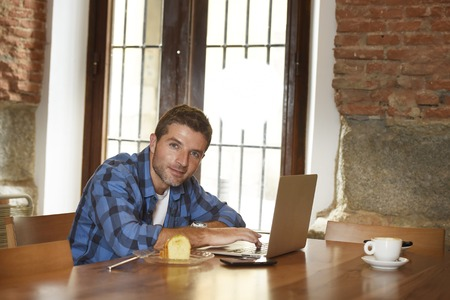 self employed: young attractive businessman or student on his 30s wearing casual clothes working or studying with laptop computer at coffee shop drinking tea cup and cake in modern business self employed concept
