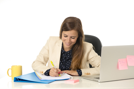 30s: corporate portrait of young attractive businesswoman on her 30s sitting at office chair working at laptop computer desk taking notes writing  on pad smiling happy Stock Photo