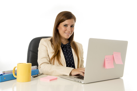 30s: corporate portrait of young attractive businesswoman on her 30s sitting at office chair working at laptop computer desk smiling happy and satisfied isolated on white background