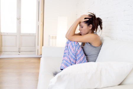 menstrual: young beautiful hispanic woman in painful expression suffering menstrual period pain lying sad on home sofa couch having tummy cramp in female health concept