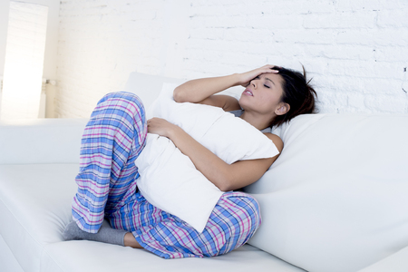 menstrual pain: young beautiful hispanic woman in painful expression holding pillow against her belly suffering menstrual period pain lying sad on home couch having tummy cramp in female health concept