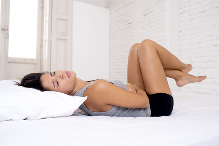 menstrual pain: young beautiful hispanic woman in painful expression holding her belly suffering menstrual period pain lying sad on home bed having tummy cramp in female health concept Stock Photo