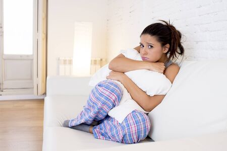 menstrual: young beautiful hispanic woman in painful expression holding pillow against her belly suffering menstrual period pain lying sad on home couch having tummy cramp in female health concept