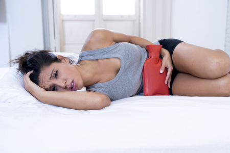 menstrual pain: young beautiful hispanic woman in painful expression holding hot water bottle against belly suffering menstrual period pain lying sad on home bed having tummy cramp in female health concept