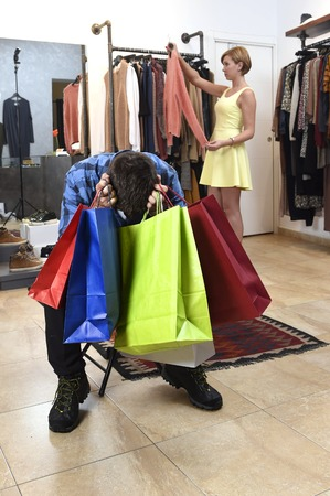 young couple shopping with man tired and bored holding lot of bags and woman happy looking for dress buying clothes at fashion store in relationship and shopaholic concept Stock Photo
