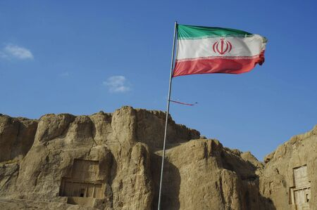 fars: Naqsh-e Rustam Persian ancient necropolis northwest of Persepolis in Fars Province Iran with Iranian flag and ancient rock relief in the cliff from Achaemenid  Empire and Sassanid period Stock Photo