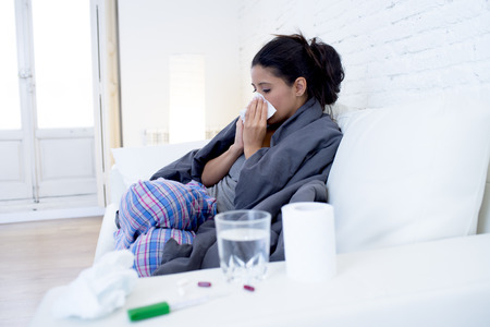 gripe: young attractive hispanic woman lying sick at home couch in cold and flu sneezing nose with tissue covering with blanket in gripe disease symptom and health care concept