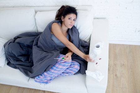 young attractive hispanic woman lying sick at home couch in cold and flu taking temperature with thermometer covered with blanket in gripe disease symptom and health care concept Stock Photo