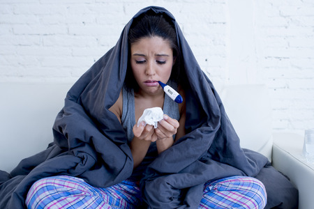 gripe: young attractive hispanic woman lying sick at home couch in cold flu sneezing nose with tissue using thermometer covered with blanket in gripe disease symptom and health care concept