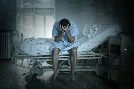 young desperate man sitting at hospital bed alone sad and devastated suffering depression crying at clinic for serious disease diagnose worried in fear on grunge dirty background Stockfoto
