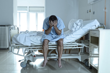 jonge wanhopige man zit op het ziekenhuisbed alleen verdrietig en verwoeste lijden depressie huilen kliniek voor ernstige ziekte te diagnosticeren gevoel bezorgd en in angst over de gezondheid