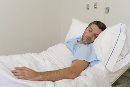 young patient man lying at hospital bed resting tired looking sad and depressed worried about medical condition suffering disease feeling sick in health care and clinical attention concept