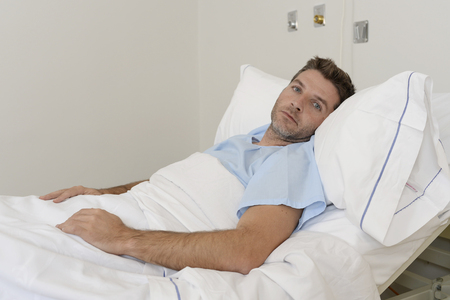doped: young patient man lying at hospital bed resting tired looking sad and depressed worried about medical condition suffering disease feeling sick in health care and clinical attention concept