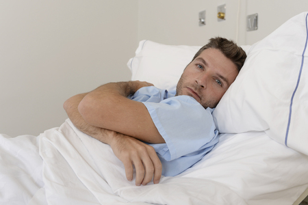 care about the health: young patient man lying at hospital bed resting tired looking sad and depressed worried about medical condition suffering disease feeling sick in health care and clinical attention concept