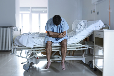 young desperate man sitting at hospital bed alone sad and devastated suffering depression crying at clinic for serious disease diagnose feeling worried and in fear about health