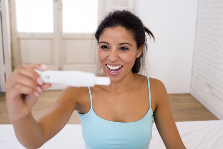 young beautiful latin woman holding pregnancy test looking and finding positive result smiling happy and excited on her bed knowing she is pregnant in female expecting and maternity concept Stock Photo