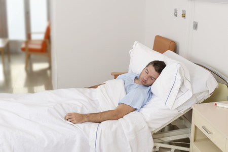 doped: young patient man lying at hospital bed resting and sleeping having serious  medical condition disease feeling sick in health care and clinical attention concept Stock Photo