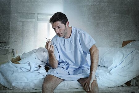 anti smoking: young attractive man looking sad and worried at hospital bed smoking cigarette in clinic bedroom looking defiant in lung cancer diagnose and anti tobacco advertising campaign concept Stock Photo